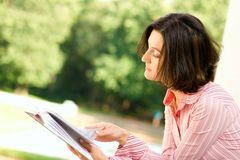 Woman with book. Portrait of attractive woman reading in the park Stock Images