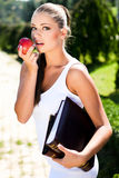 Woman with book and apple Stock Images