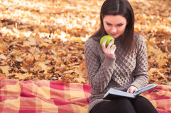 Woman with book and apple sitting on a rug Royalty Free Stock Image