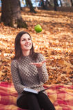 Woman with book and apple sitting on a rug Stock Images