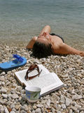 Woman with book on beach. Attractive alone  brunette after swimming-lying wet on the beach - pebbles and beside it is an open book, cup of coffee, sunglasses and Stock Photo