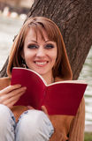Woman and book. Beautiful young woman reading a book, smiling in nature Stock Photography