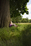 Woman With Book Beneath A Tree Royalty Free Stock Images