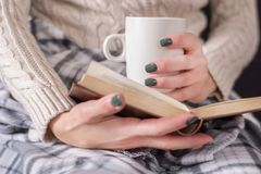 Woman with book and cup of coffee in hand wears sweater stock images