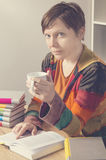 Woman with a book and cup of hot drink. Royalty Free Stock Image