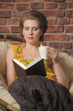 Woman with a book and a cup of tea Stock Images