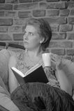 Woman with a book and a cup of tea Royalty Free Stock Photos