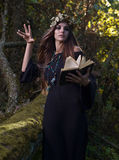 Woman with book in dark forest Royalty Free Stock Image