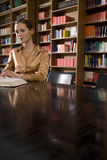 Woman With Book At Desk In Library Stock Photography