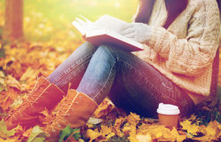 Woman with book drinking coffee in autumn park Royalty Free Stock Photo