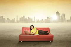 Woman with book and laptop on the couch Stock Photos