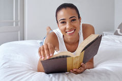 Woman book laying bed. Young woman laying relaxing on bed reading literature novel story book at home Stock Images