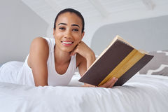 Woman book laying bed. Young woman laying relaxing on bed reading literature novel story book at home Royalty Free Stock Photo