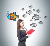 Woman with a book and a leader fish. Side view of young woman wearing a dress and reading a red book standing near a gray wall with fish. One of them is bright Royalty Free Stock Photography