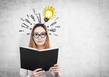 Woman with book and light bulb, exclamations Royalty Free Stock Photos
