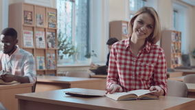 Woman with book looking at camera stock video footage