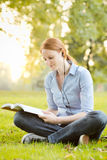 Woman with a Book and Music in a Park Royalty Free Stock Photography