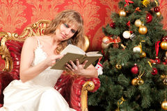 Woman with book near the Christmas tree Stock Photos
