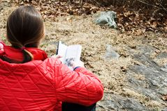 Woman with a book outdoors. A hiker reading a trail book to find directions. Or it could just be a woman reading a book outdoors. Communing with nature royalty free stock image