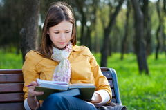 Woman with book in park Stock Photo