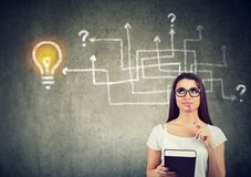 Woman with a book and pen brainstorming. On new study project standing near a wall with arrow maze and a bright idea light bulb sketch on it royalty free stock photography