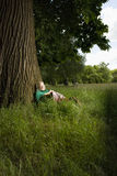 Woman With Book Sitting Beneath Tree Royalty Free Stock Photography