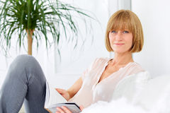 Woman with book sitting on the sofa Stock Photo