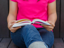 Woman with book sitting Stock Photography