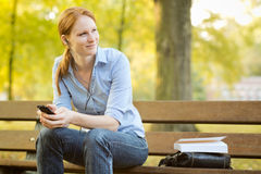 Woman with a Book and Smartphone in a Park Royalty Free Stock Images