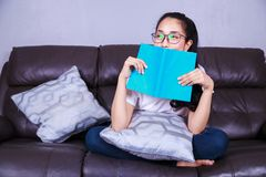 Woman with a book on sofa at home Royalty Free Stock Photos