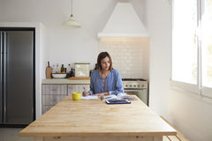 Woman with book and tablet computer writing at kitchen table Royalty Free Stock Photos