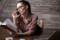 Woman with book talking on phone Stock Photography