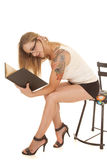 Woman book tattoo lean forward sit Stock Photography