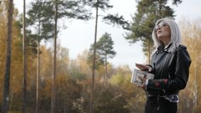 Woman with book walking in park stock footage