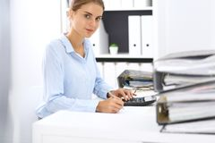Woman bookkeeper or financial inspector calculating or checking balance, making report. Internal Revenue Service at work. With financial document. Tax and audit stock photo