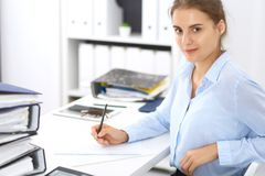 Woman bookkeeper or financial inspector calculating or checking balance, making report. Internal Revenue Service at work. With financial document. Tax and audit stock photography