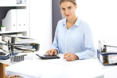 Woman bookkeeper or financial inspector calculating or checking balance, making report. Internal Revenue Service at work. With financial document. Tax and audit stock image