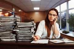 Woman bookkeeper using mobile phone at workplace. Young woman bookkeeper using mobile phone at workplace, stacks of documents on the table Royalty Free Stock Photography