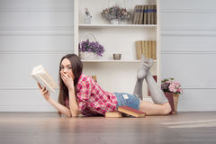 Woman with books. Cheerful young woman with books lies in the room with shelves Royalty Free Stock Image