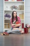 Woman with books. Cheerful young woman with books sitting in the room with shelves Royalty Free Stock Photo