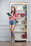 Woman with books. Cheerful young woman with books standing in the room with shelves Royalty Free Stock Images