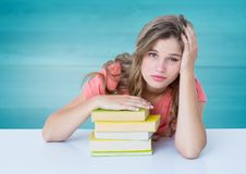 Woman with books at desk against blurry blue wood panel stock photography
