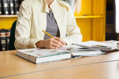 Woman With Books And Pencil Sitting At Table In Royalty Free Stock Photos