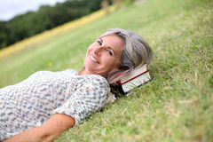 Woman with books relaxing in garden Stock Photo