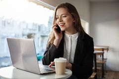 Woman books tickets for concert. Portrait of good-looking caucasian girl sitting in cafe, drinking coffee, talking on. Smartphone, looking at laptop screen with Royalty Free Stock Photo
