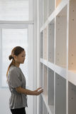 Woman by bookshelf Royalty Free Stock Photography