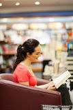 Woman in bookstore. Young woman reading a book in bookstore stock images