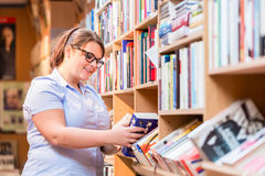 Woman in bookstore looking for book Stock Photography