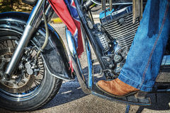 Woman boot on a classic motorcycle floorboard Royalty Free Stock Image