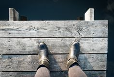 Woman in boots on the pier takes a step into the water, from above,. Woman in black boots on the pier takes a step into the water, from above Stock Photos